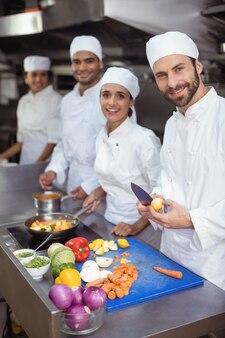 Повара режут овощи на разделочной доске на коммерческой кухне