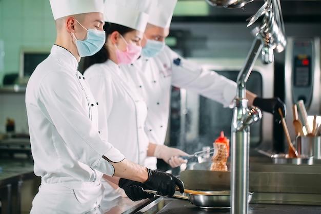 保護マスクと手袋のシェフがレストランやホテルのキッチンで料理を準備します。