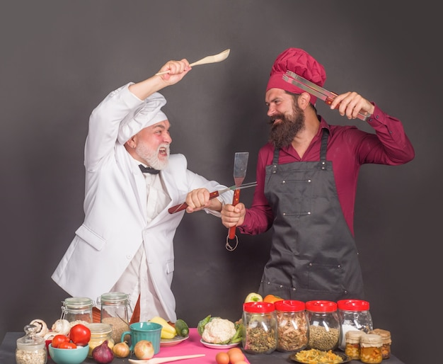 Chefs on kitchen. two chefs fighting on kitchen. kitchen. cooking. beared chef man. male chef in uniform. chef, cook or baker.