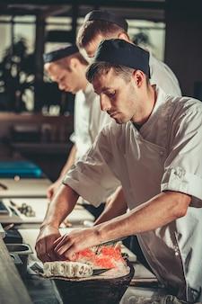 Повара делают роллы маки на кухне