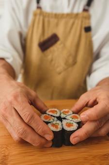 연어 생선과 야채로 스시 롤을 만드는 요리사 남성 손