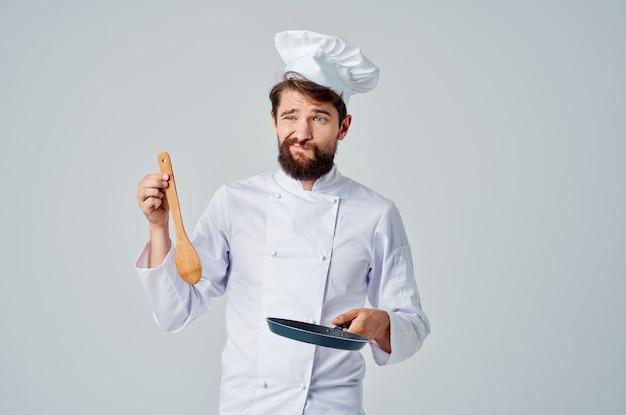フライパンを手に持ったシェフがレストランのプロを料理