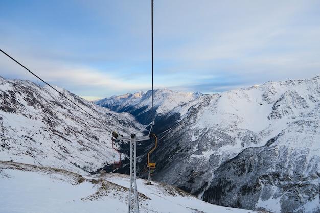 Cheget 스키 리프트. 구름 푸른 하늘에 백인 산의 눈 덮인 봉우리