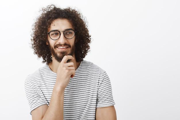 それをチェックしてください。遊び心のあるロマンチックなムードで魅力的な軽薄な男、ひげに手を握って、右を見て、好奇心旺盛な表情で笑顔