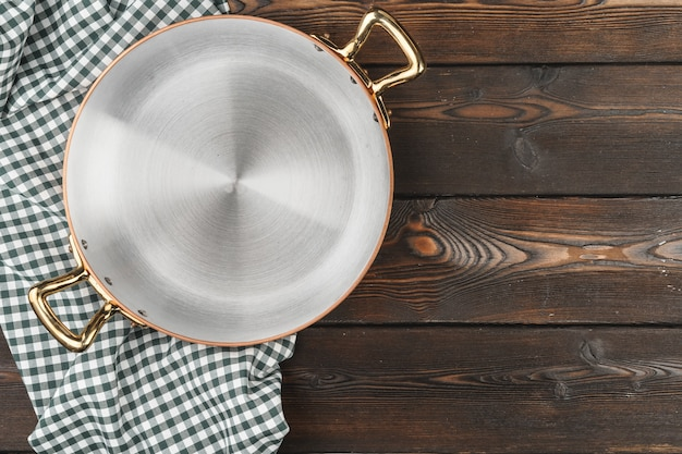 木製のテーブルにchekeredテーブルクロスと銅鍋