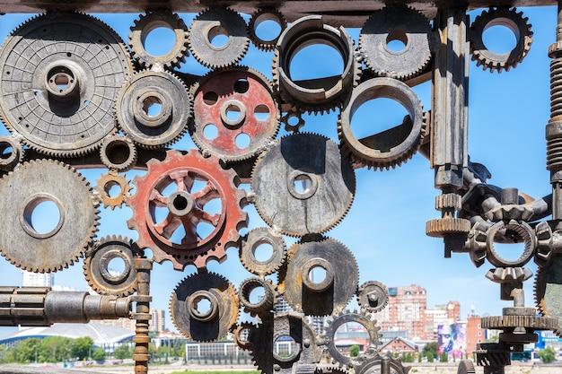 Челябинск россия 14 июня 2021 абстрактная фигура из старых автомобильных деталей металлические шестерни, валы и маховики используются как арт-объекты