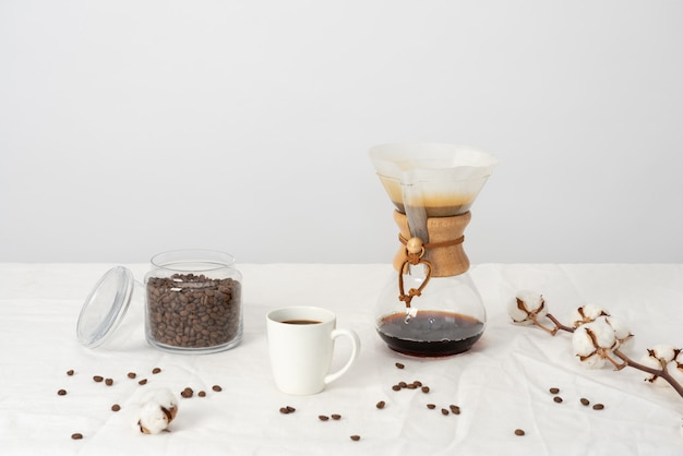 Chemex, large cup of coffee, jat of coffee beans, cotton branch