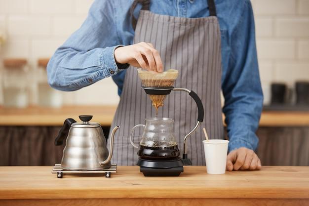 Chemexでpouronコーヒーを準備するrofessionalバーテンダーのクローズアップ。