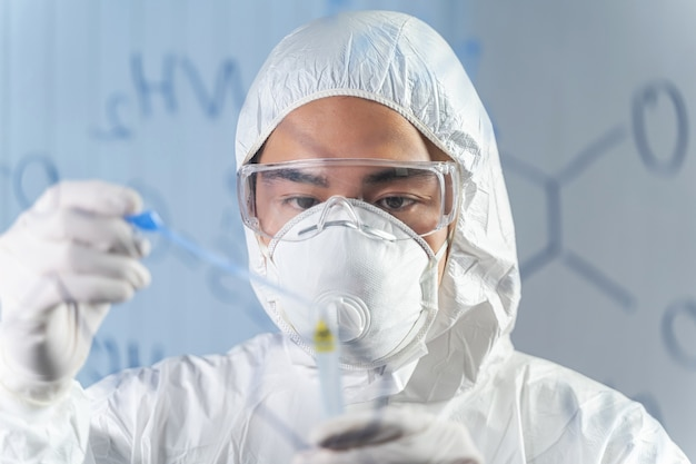 화학식. 바이러스 백신을 발명하는 동안 보호 안경과 마스크를 쓴 세심한 아시아 연구원