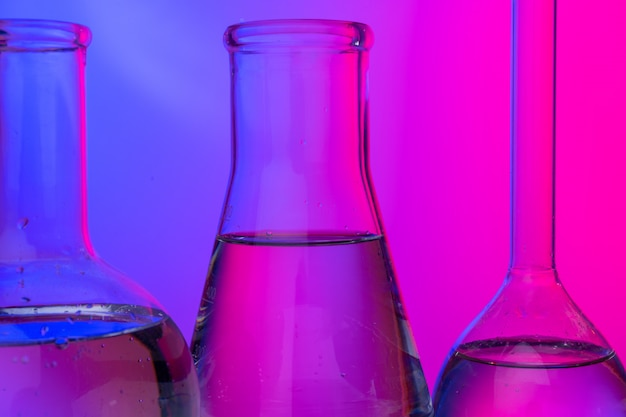 Chemical glassware close up on neon pink-purple