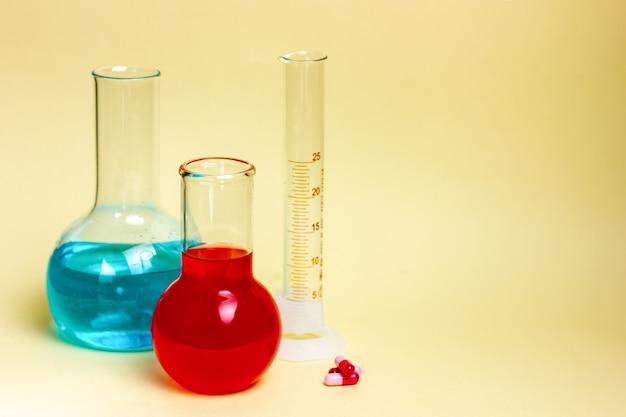 노란색 배경에 화학 유리, 플라스크 및 테스트 튜브. 제약 연구. 고품질 사진
