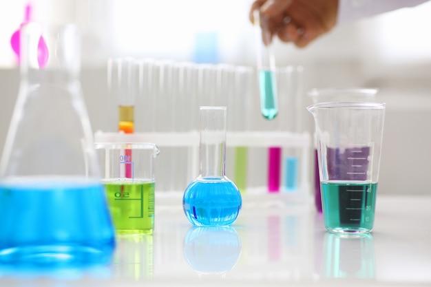 파란색 마젠타 분홍색 액체 실험실 튜브가 있는 화학 산업 전구는 액체 테스트 테스트 개발 물질 독극물 첨가제 안정제 맛 집 청소 실험실의 테이블에 서 있습니다.