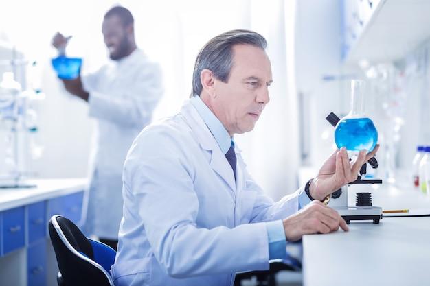 화학 실험실. 플라스크를 들고 화학 실험실에서 작업하는 동안 파란색 액체를보고 심각한 잘 생긴 똑똑한 과학자