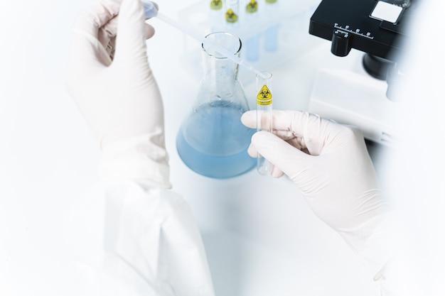 화학 연구. 보호 장갑을 끼고 시험관을 들고 있는 남성 손에 초점을 맞춘 사진