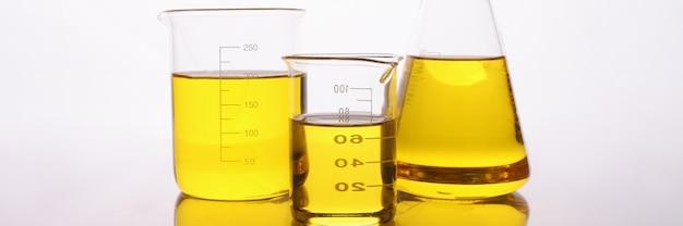 Химические пробирки и колбы с желтым маслом