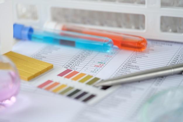 Химические пробирки с синей и оранжевой жидкостью с результатами анализа на лабораторном столе
