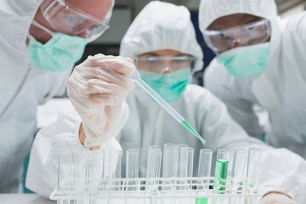 Chemist adding green liquid to test tubes as two others are watching
