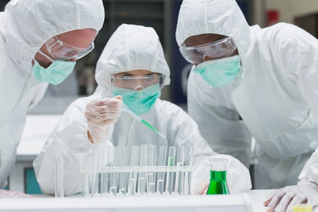 Chemist adding green liquid to test tubes with two other chemists watching
