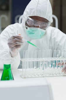 Chemist adding green liquid to test  tubes