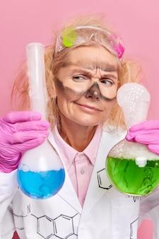 화학자는 파란색과 녹색 액체가 있는 두 개의 유리 플라스크를 들고 과학 연구를 수행하여 실험실에서 분홍색으로 격리된 유니폼을 입고 실험합니다