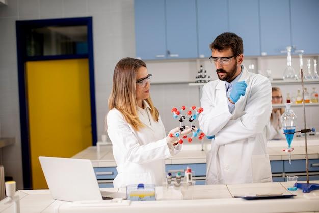 Пара химиков в защитных очках держит молекулярную модель в лаборатории