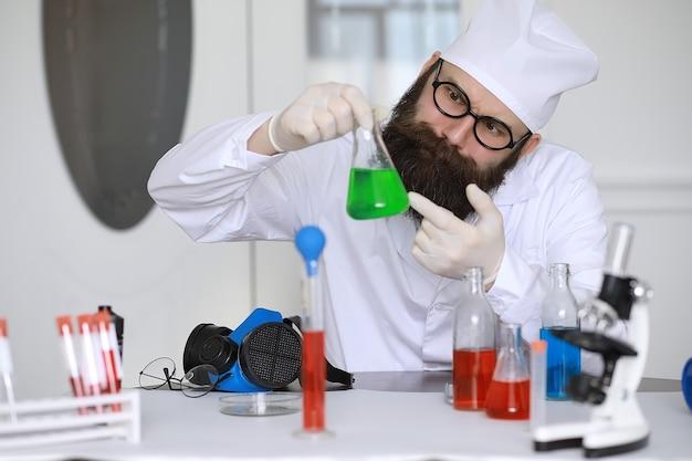 クレイジーな化学者。マッドサイエンティストが科学実験室で実験を行っています。顕微鏡を使用して研究を行います。