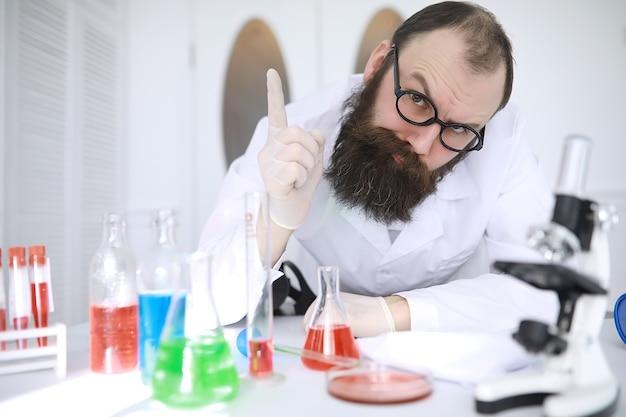 Химик сумасшедший. сумасшедший ученый проводит эксперименты в научной лаборатории. проводит исследования под микроскопом.