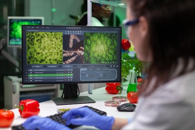 Medico chimico che analizza piante geneticamente modificate sul computer