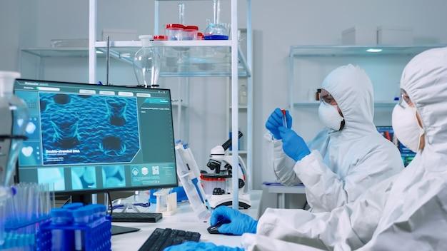 顕微鏡を使用している検査技師の間、pcで働いているppeスーツの化学者医師。 covid19ウイルスに対する治療法を研究するためのハイテクでワクチンの進化を調べる科学者のチーム