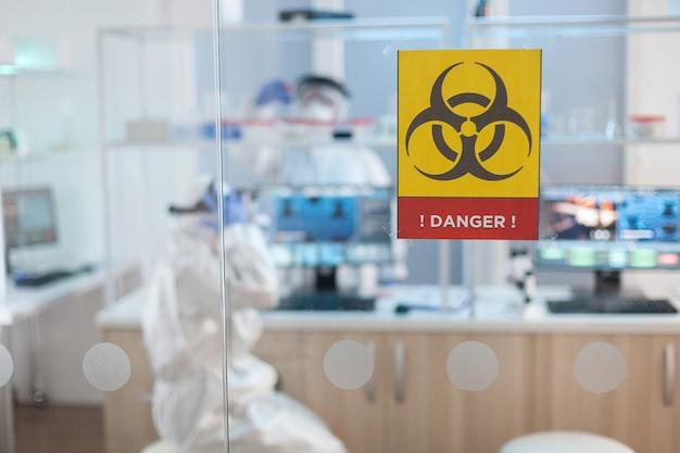 의료 실험실의 위험 지역에서 일하는 보호복을 입은 화학자 의사