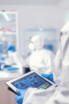 実験室でタブレットpcを保持しているコロナウイルスの保護スーツを着た化学者。 covidに対する治療を研究するためのハイテク技術を使用してワクチン開発を行っている科学者のチーム
