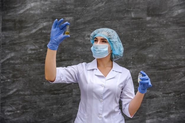 물질과 테스트 튜브를 검사하는 화학자. 그녀는 보호 복을 입고