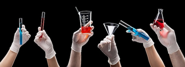 Chemist hands holding laboratory glassware with liquids on black space