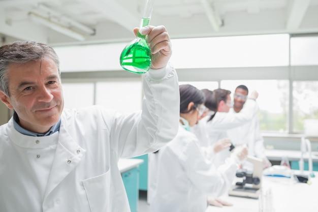Chemist happily holding beaker