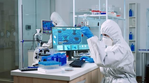 장비를 갖춘 실험실에서 컴퓨터로 메모를 하는 혈액 샘플을 검사하는 작업복을 입은 화학자. covid19 바이러스에 대한 진단을 연구하는 첨단 기술을 사용하여 백신 진화를 조사하는 의사 팀