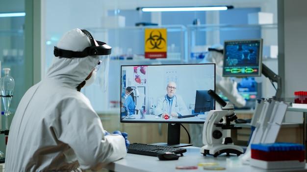 ビデオ通話でプロの医師を聞いているppeスーツの化学者、研究所での仮想会議中に話し合っています。 covid19ウイルスに対する治療法を研究するためにハイテクを使用している医師
