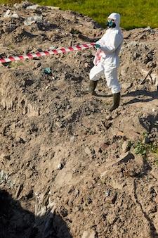 Химик в защитном костюме, отделяющий опасную зону лентой на открытом воздухе
