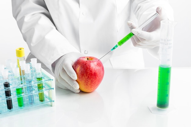 Chemist injecting apple with chemicals in tubes