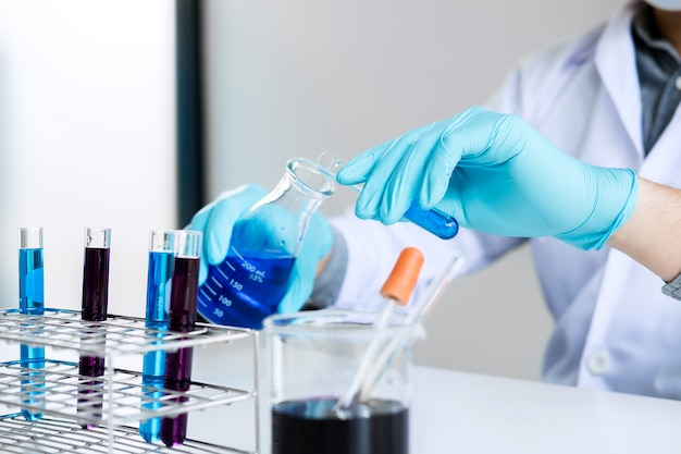 Chemist is analyzing sample in laboratory with equipment and science experiments glassware containing