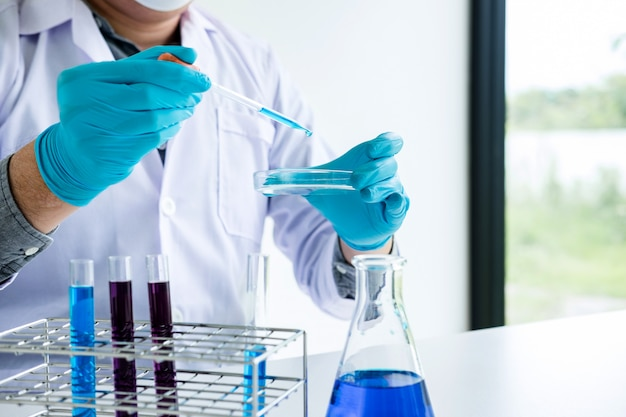 Chemist is analyzing sample in laboratory with equipment and science experiments glassware