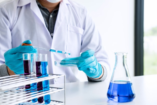 Chemist is analyzing sample in laboratory with equipment and science experiments