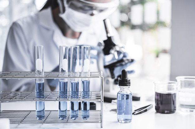 Chemist is analyzing sample in laboratory with microscope