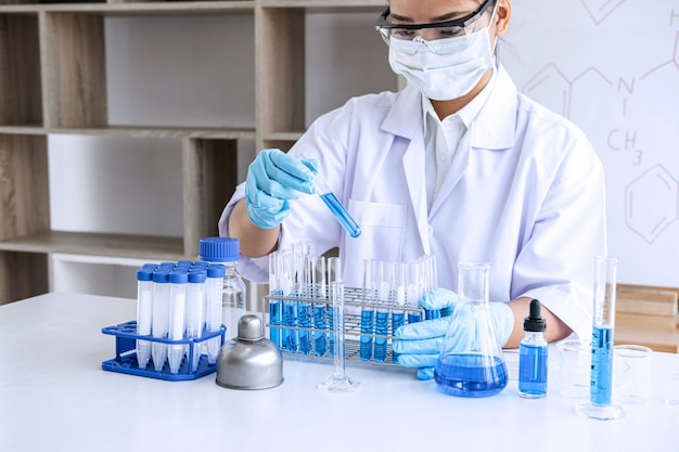 Chemist is analyzing sample in laboratory with tool