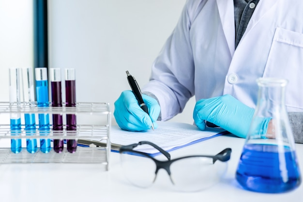 Chemist is analyzing sample and record in laboratory with equipment and science experiments glassware containing