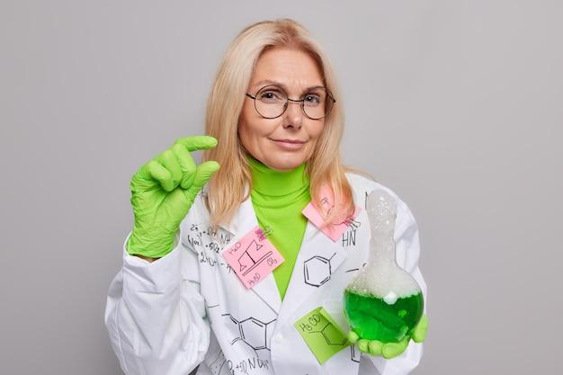 화학자 실험실은 회색 벽에 격리된 흰색 코트 고무 코트를 입고 유리 플라스크에 녹색 버블링 액체를 보유하고 있는 결과에 대해 작은 제스처를 보여줍니다.