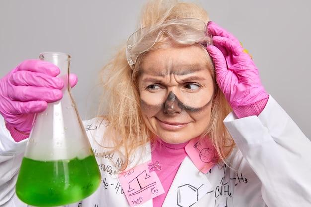 Химик внимательно смотрит на стакан с зеленой жидкостью работает в лаборатории одетый в униформу попадает жидкость в результате смешивания реагентов
