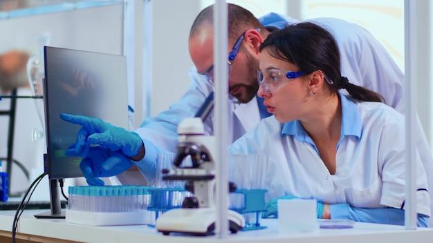 化学者の看護師が、コンピューターのデスクトップを指す近代的な設備の整った実験室での医師のワクチン開発について説明します。ハイテク研究診断を使用してウイルスの進化を調べる医師のチーム