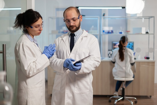 현대 실험실에서 의사에게 백신 개발을 설명하는 화학자 간호사