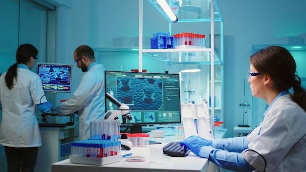 Covid19 바이러스에 대한 첨단 연구 치료법을 사용하여 바이러스 진화를 검사하는 과학 장비 실험실에 앉아 화학자 간호사