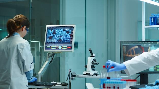 夜に科学的な近代的な設備の整った実験室でコンピューターに取り組んでいる化学者の看護師。 covid19ウイルスに対する治療法を研究するハイテク技術を使用してワクチンの進化を調べるもの